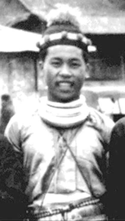 Xyooj i sin hmong-drakt med en svart lue med dusk og tre halskjeder av sølv som han hadde fått av sin far og som han var svært stolt av